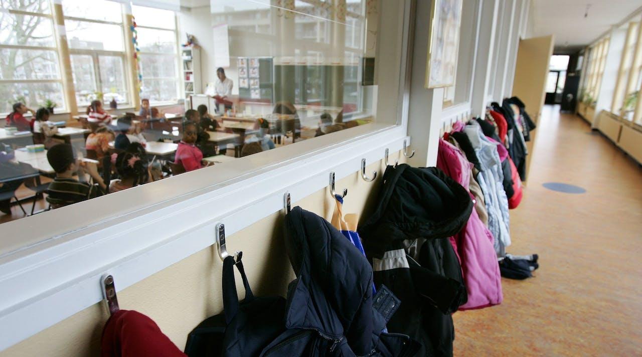 Gang met jassen en leerlingen in klaslokaal van de Petrus Donders school in Den Haag.