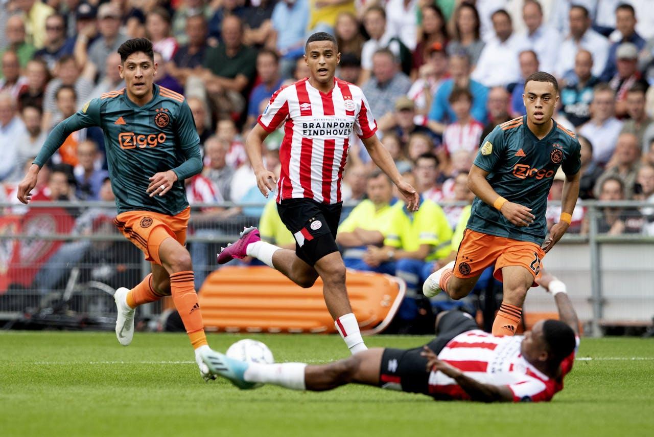 Steven Bergwijn van PSV ligt op de grond. Achter hem Edson Alvarez, Sergino Dest en Mohammed Ihattaren van PSV. PSV speelt in de eredivisie tegen Ajax.