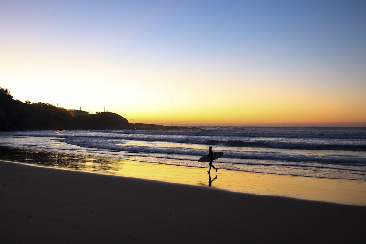 Een surfer loopt over het strand in Sydney, Australië.