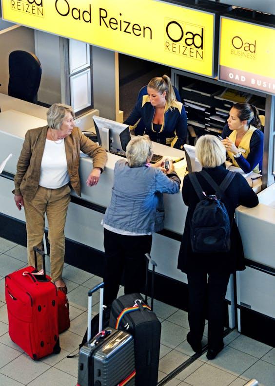 Reizigers informeren bij de Oad-balie op Schiphol.