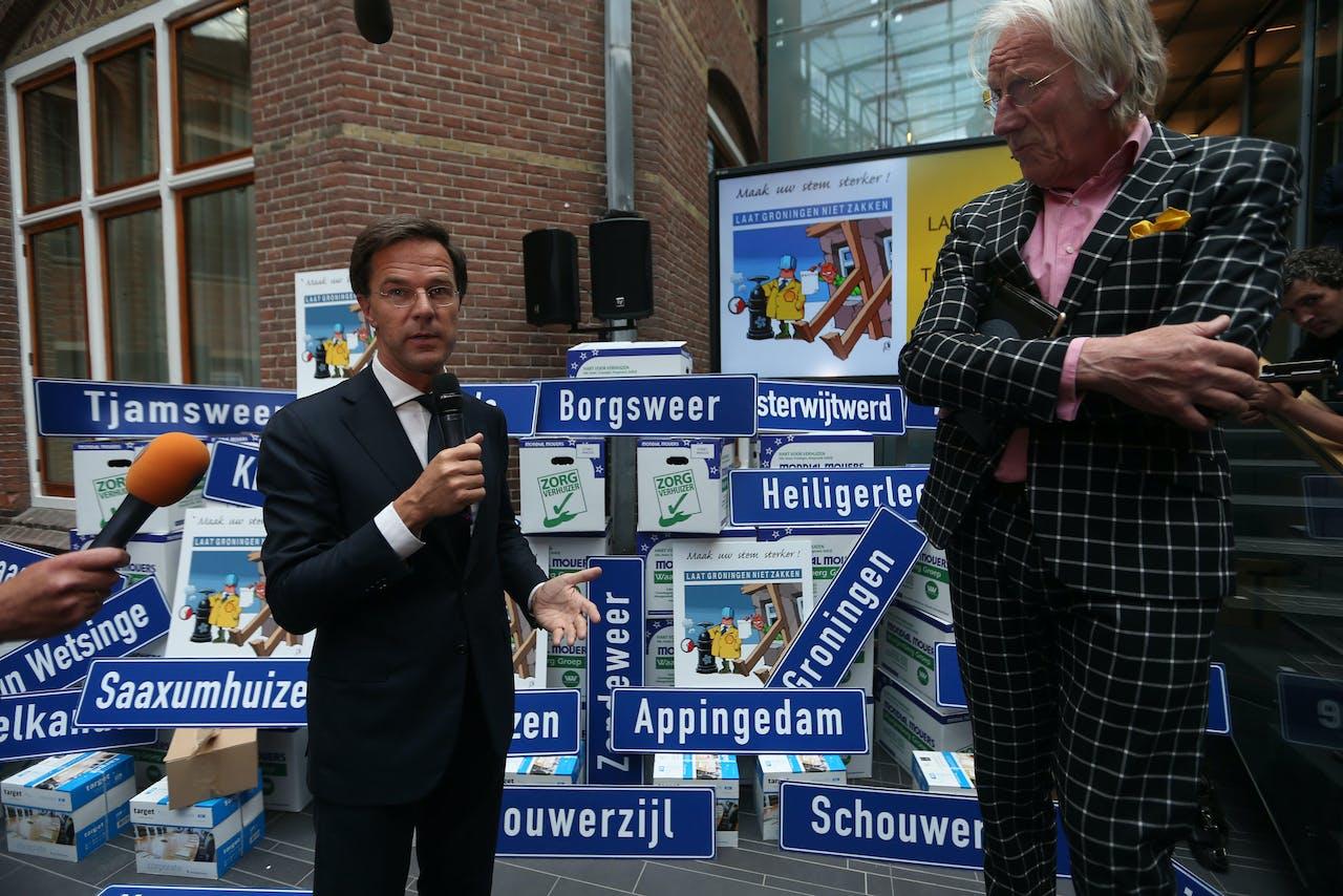 Groningen- Demissionair premier Mark Rutte tijdens een werkbezoek aan Groningen om te praten over de aardbevingsproblematiek. Hij spreekt onder meer met burgemeesters, provinciebestuurders, de Groninger Bodem Beweging en het Groninger Gasberaad. Overhandiging petitie 'laat Groningen niet zakken' door Freek de Jonge . ANP CATRINUS VAN DER VEEN