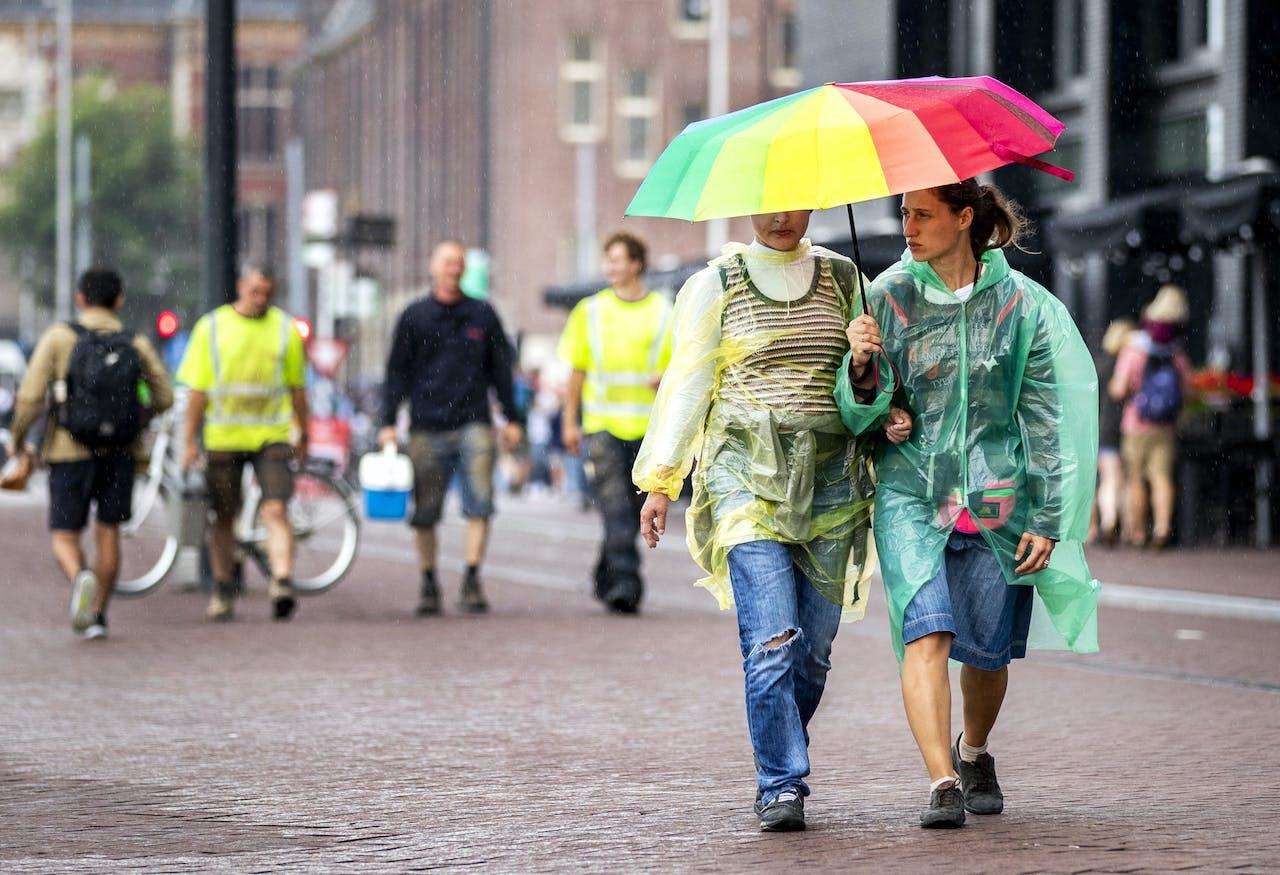 2018-08-09 15:31:47 AMSTERDAM - Toeristen en Amsterdammers in de regen. Na een lange periode van droog weer valt er op veel plaatsen veel regen. ANP REMKO DE WAAL