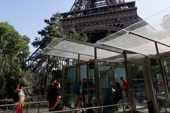 Bezoekers dragen mondkapjes bij de ingang van de Eiffeltoren