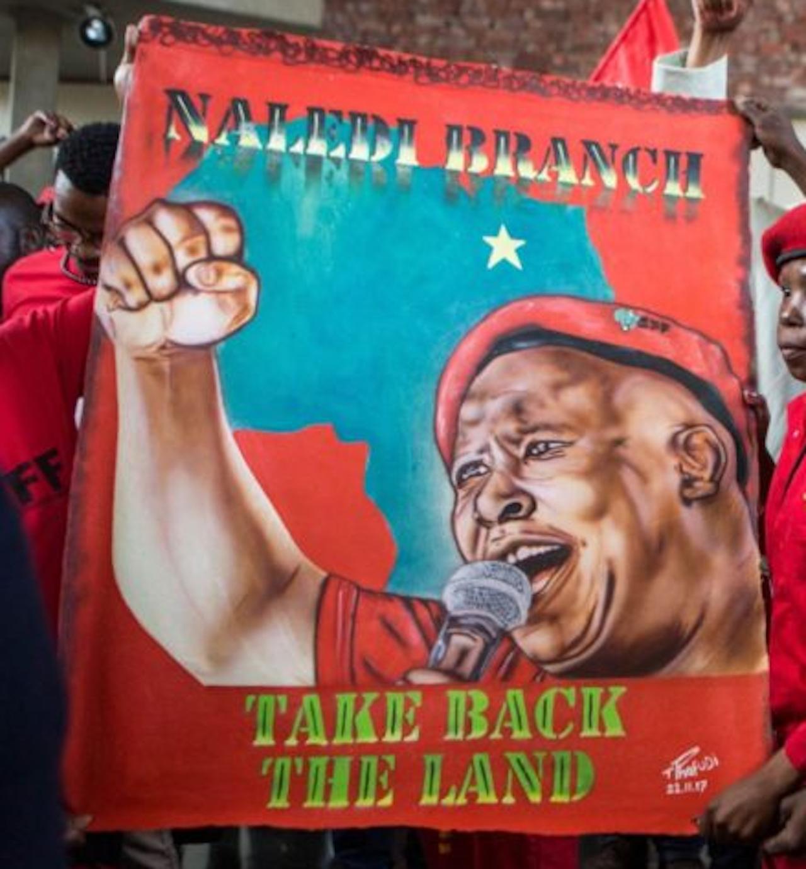 Een poster met oproep om land van blanke boeren terug te eisen.