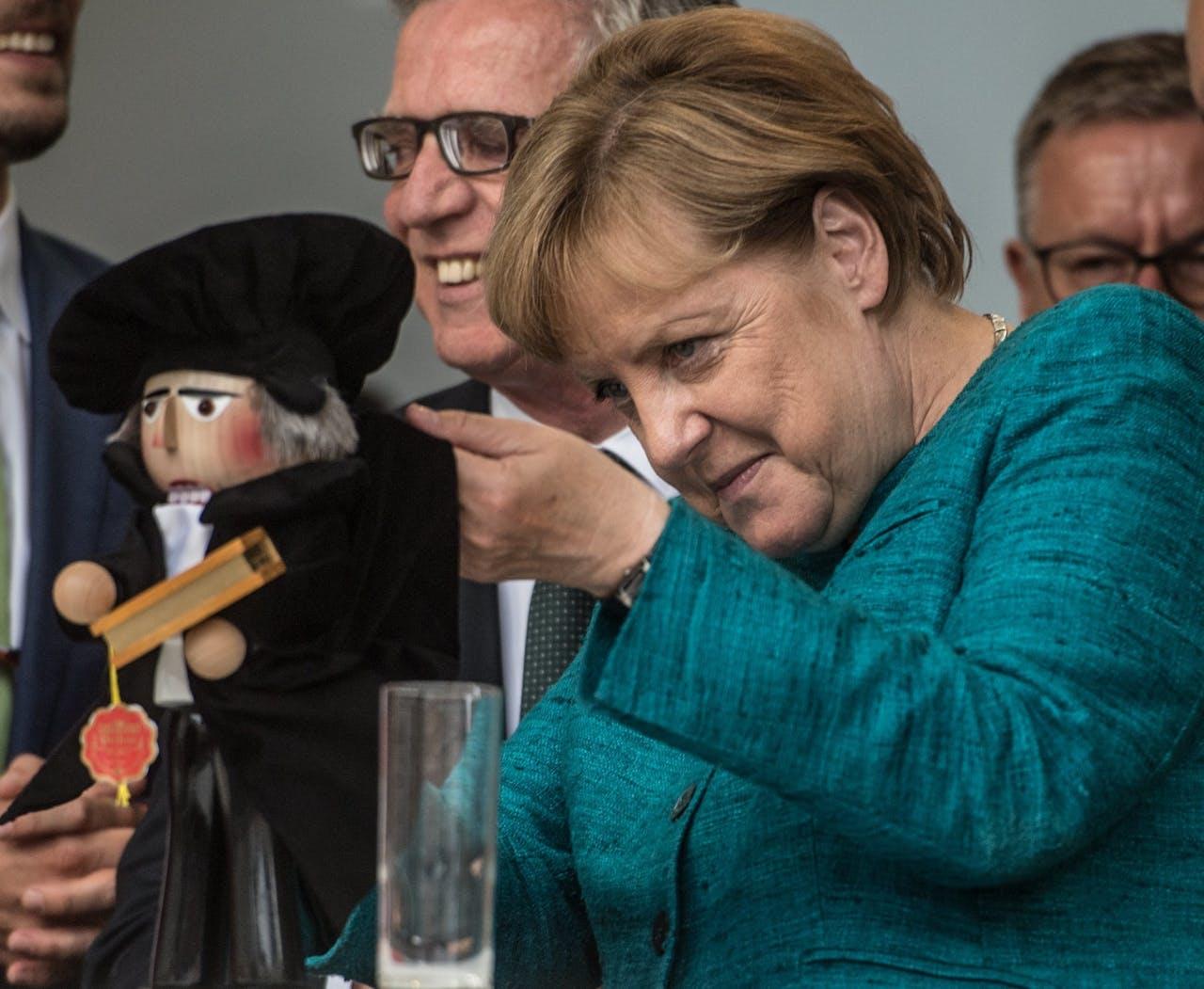 Het Lutherjubileum wordt in Duitsland groots gevierd. Bondskanselier Angela Merkel houdt een Luther-handpoppetje vast tijdens een campagnebijeenkomst van haar partij (CDU).
