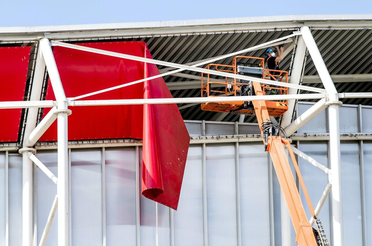 Een hoogwerker bij het dak van het AFAS Stadion van AZ. De Onderzoeksraad voor Veiligheid begint een onderzoek naar het gedeeltelijke instorten van het stadiondak.
