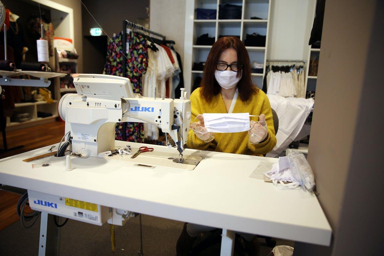 Een medewerker van een kledingwinkel maakt mondkapjes.