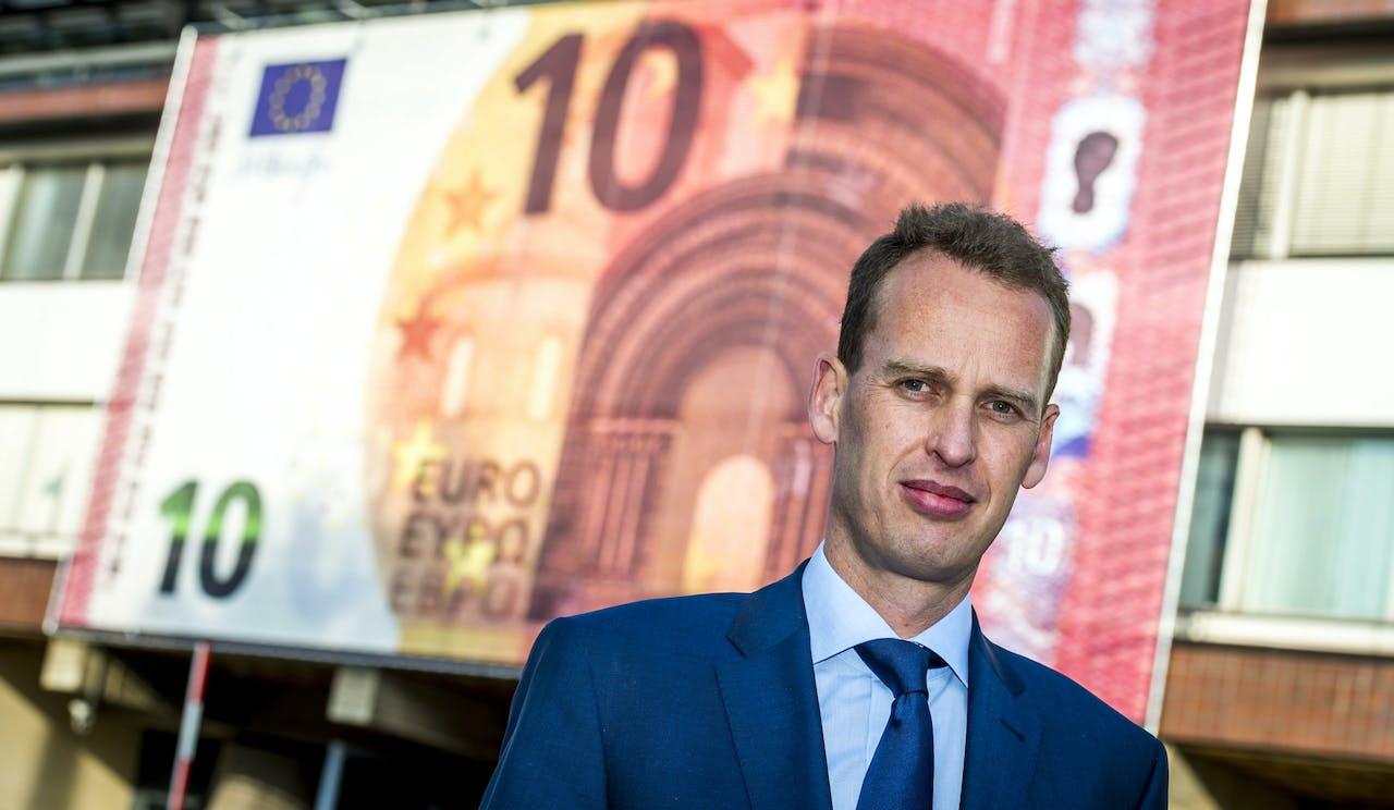 Frank Elderson poseert voor een banner met een beeltenis van het nieuwe biljet van tien euro aan de gevel van De Nederlandsche Bank.