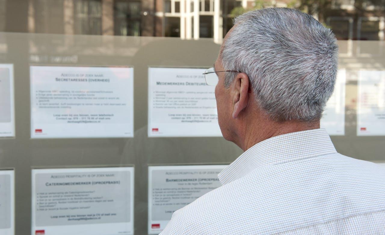 Een oudere man bekijkt vacatures bij een uitzendbureau. Voor veel oudere en laagopgeleide werkzoekenden blijft het moeilijk werk te vinden.