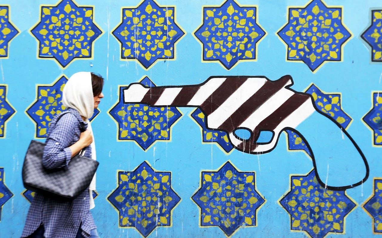 Een Iraanse vrouw loopt langs een muurschildering bij de voormalig Amerikaanse ambassade in Teheran.